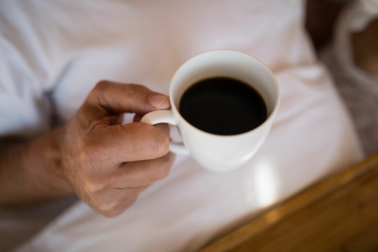 Mid section of man having black coffee during morning
