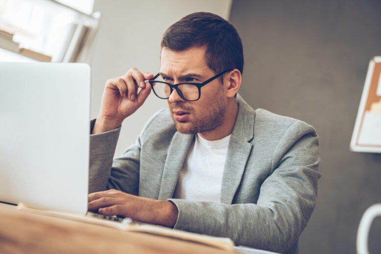 Handsome young man looking at his laptop and adjusting his glasses while sitting at his working place