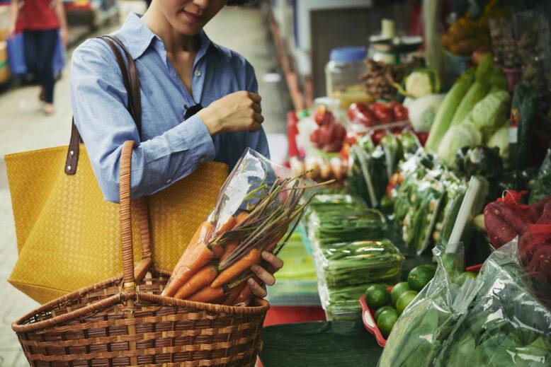 Woman buying big basket of vegetables at food market