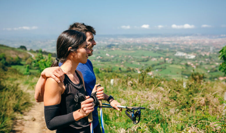 Young couple stopping to look at the views of the city while doing trail