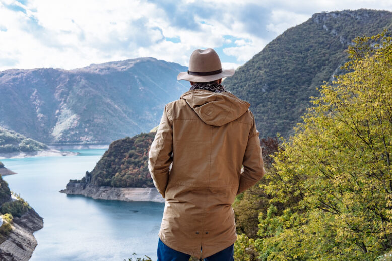 Traveler on the background The famous Piva Canyon with its fantastic reservoir.