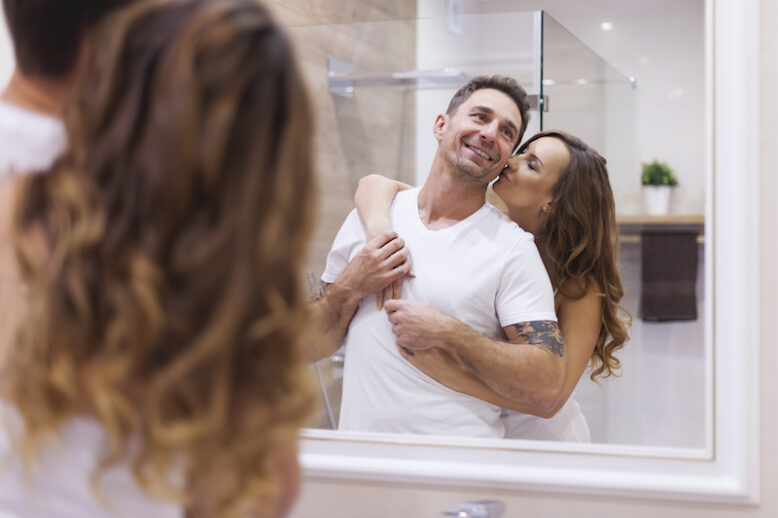 man and woman hugging in front of the bathroom mirror