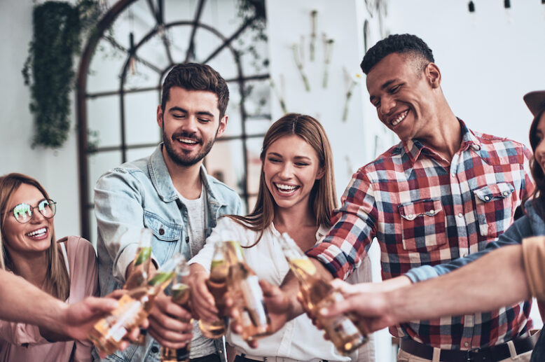 Cheers!  Group of young people in casual wear toasting each other and smiling while having a party indoors