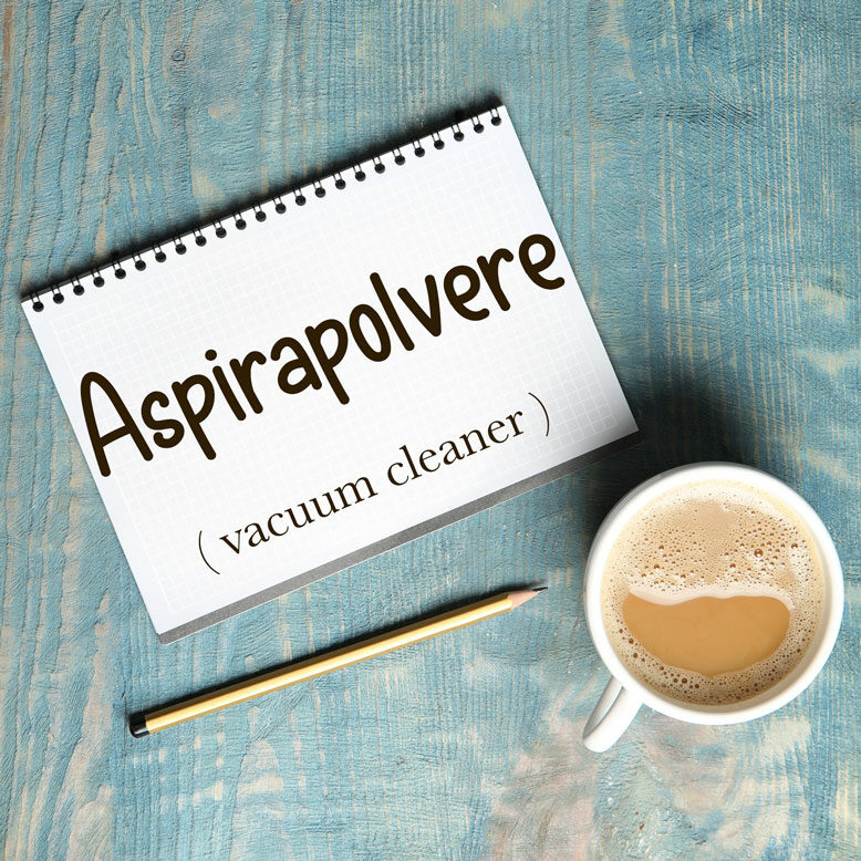 """cover image with the word """"aspirapolvere"""" and its translation written on a notepad next to a cup of cofee"""