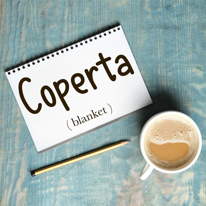 """cover image with the word """"coperta"""" and its translation written on a notepad next to a cup of cofee"""