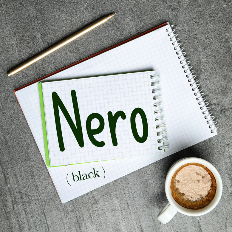 """cover image with the word """"nero"""" and its translation written on a notepad next to a cup of cofee"""