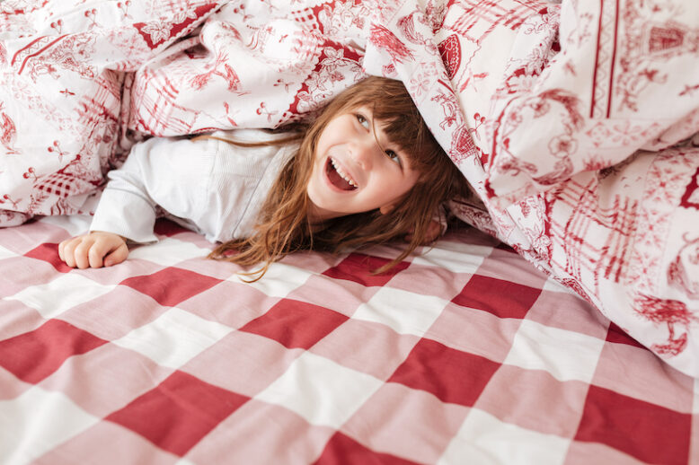 Happy little girl lying on checkered bed under blanket