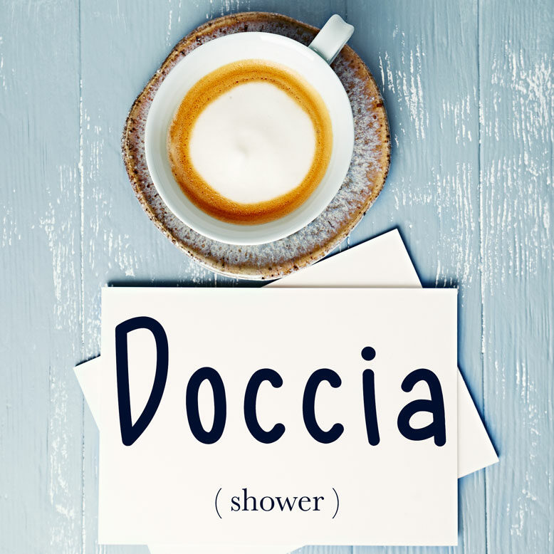 """cover image with the word """"doccia"""" and its translation written on a notepad next to a cup of cofee"""