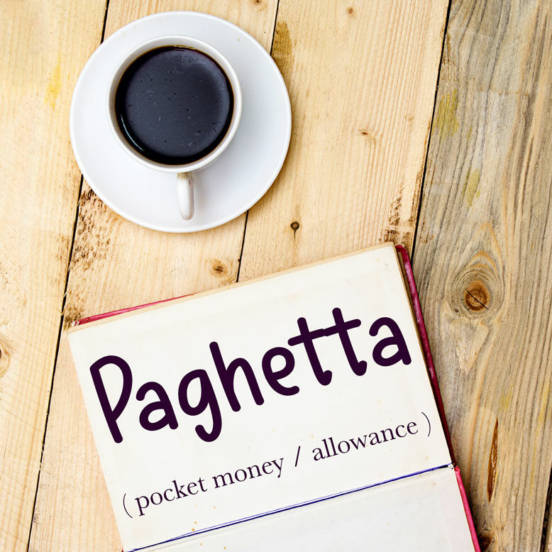 """cover image with the word """"paghetta"""" and its translation written on a notepad next to a cup of cofee"""