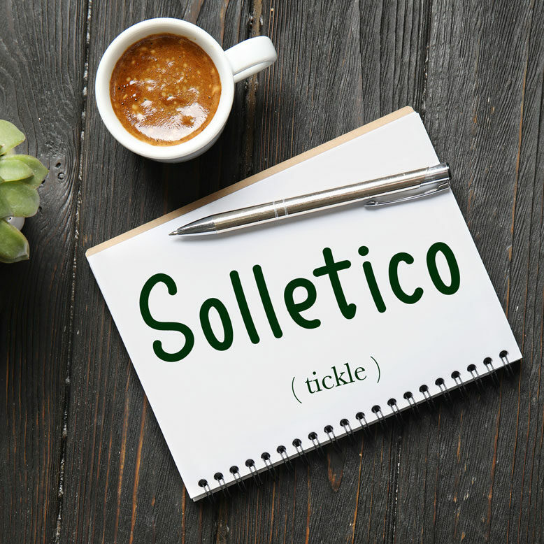 """cover image with the word """"solletico"""" and its translation written on a notepad next to a cup of cofee"""