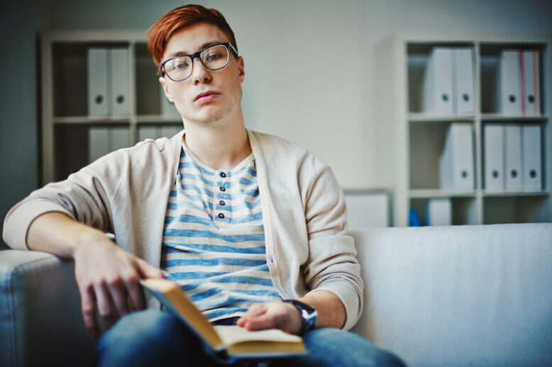 Bored guy with open book looking at camera