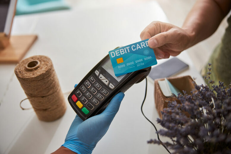 Hand of a Caucasian male pressing a banking card to a point-of-sale terminal at the counter of flower store