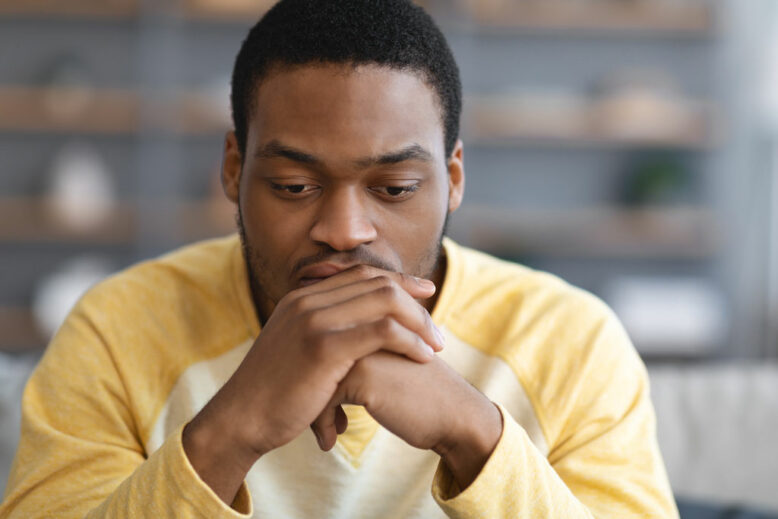 Pensive african american young man leaning on his hands and looking down, thinking about something, closeup portrait, copy space.