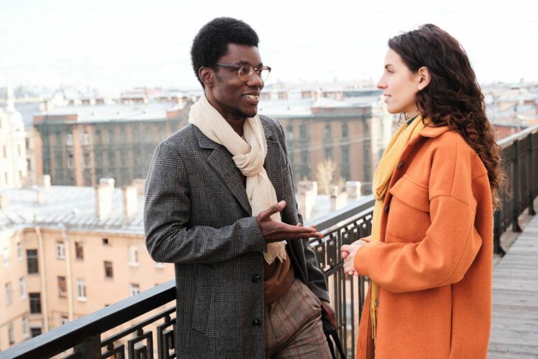 Man and woman talking to each other while standing on balcony outdoors