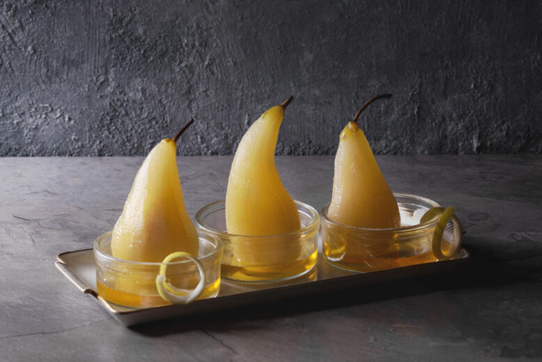 poached pears in white wine served in glass bowls with syrup and lemon zest over gray texture table