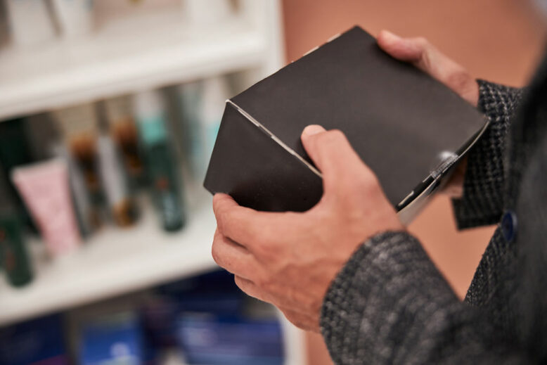 cropped photo of man hands holding a black cardboard box inside the shop