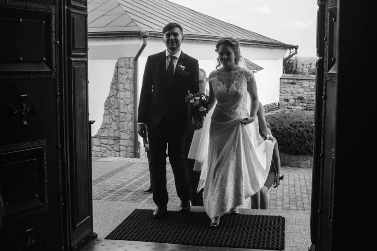 Happy couple entering church, beautiful bride in white wedding dress and handsome groom near church entrance going to wedding ceremony