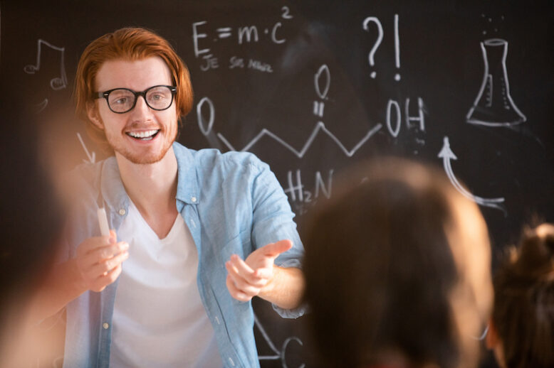 Young cheerful teacher in eyeglasses pointing at one of students giving right answer to his question at lesson