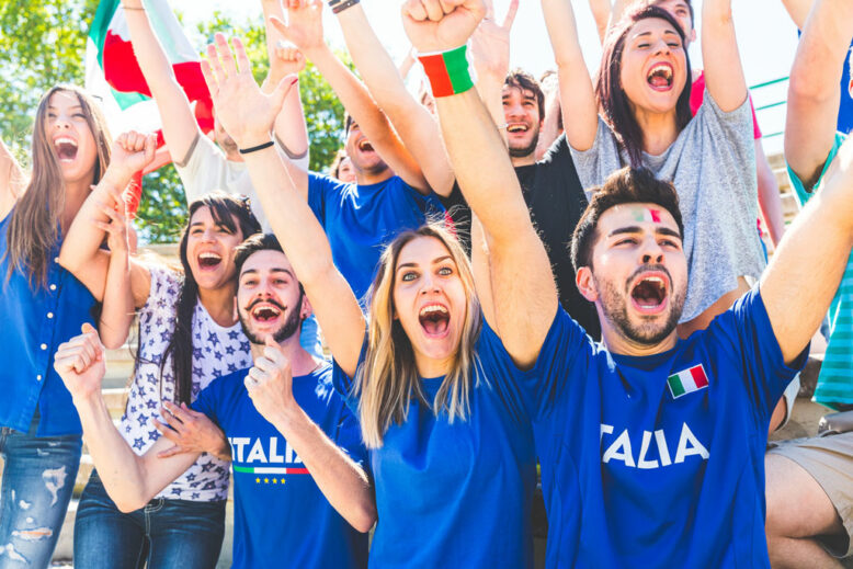 italian supporters wearing blue shirts, cheering with their hands in the air