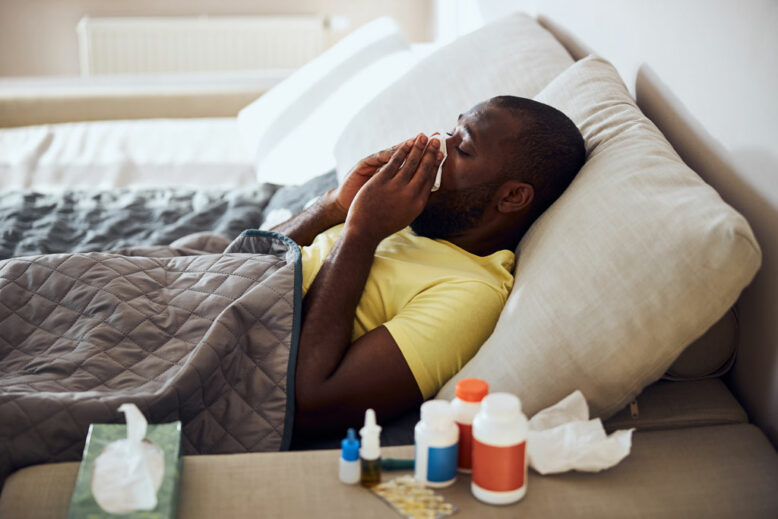 Man falling ill and blowing the snots into a tissue while lying under cover