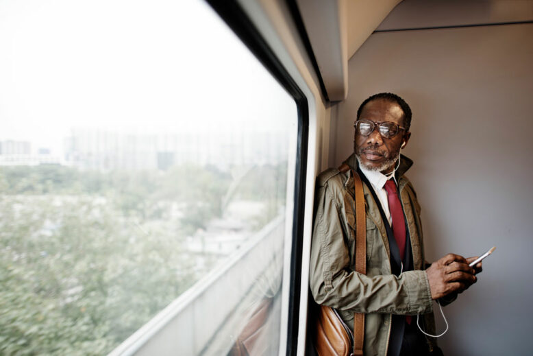 Man Traveling, standing up and looking through the window, holding his phone with earphones in his ears