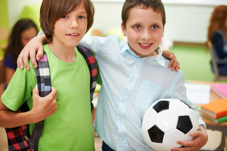 two boys smiling with hand over the shoulders over each others, one holding a foot ball