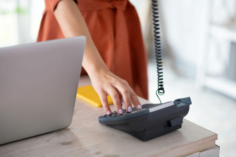 Close up of woman dialing number while working in the office