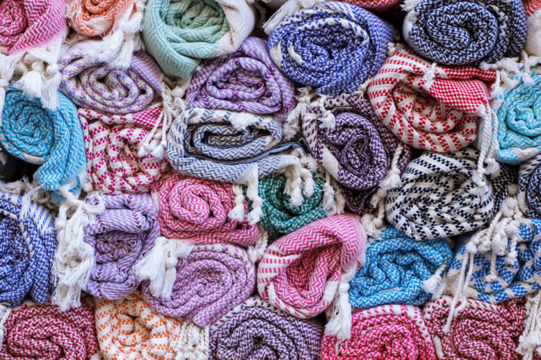 Colorful blankets, rolled up in a roll on the old market, traditional textiles.