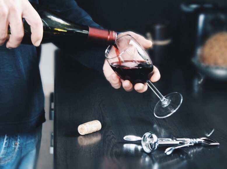 male hand pouring red wine in a wine glass