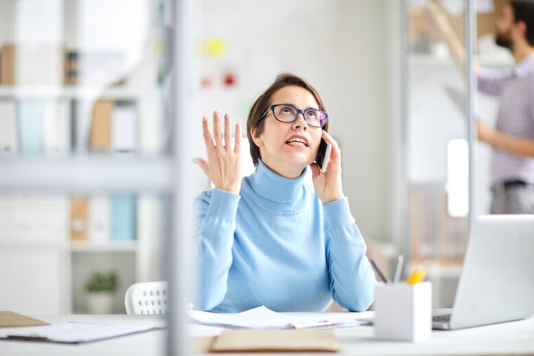Annoyed office manager explaining something to client on the phone while sitting by desk in office