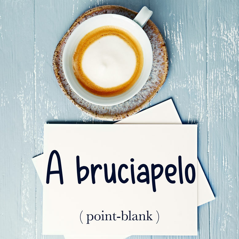 """cover image with the word """"A bruciapelo"""" and its translation written on a notepad next to a cup of cofee"""