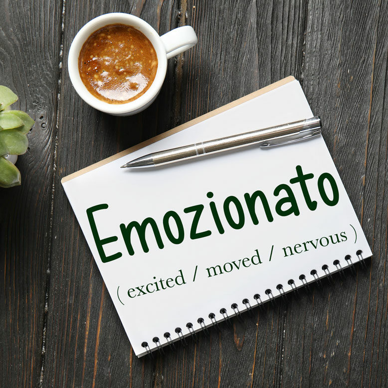 """cover image with the word """"emozionato"""" and its translation written on a notepad next to a cup of coffee"""