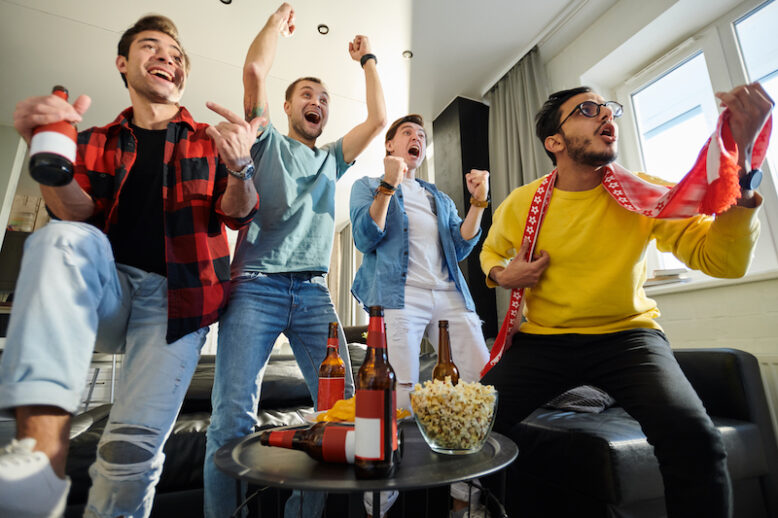 Excited young men watching sports competition at home, happy fans victoriously screaming