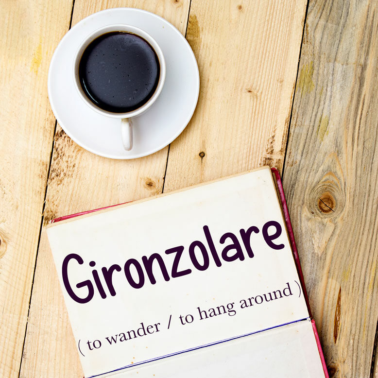 """cover image with the word """"gironzolare"""" and its translation written on a notepad next to a cup of cofee"""