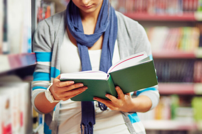 Student of college reading book in library