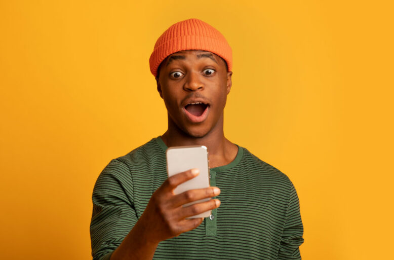 surprised african american man standing with opened mouth on yellow background, emotionally reacting to online news