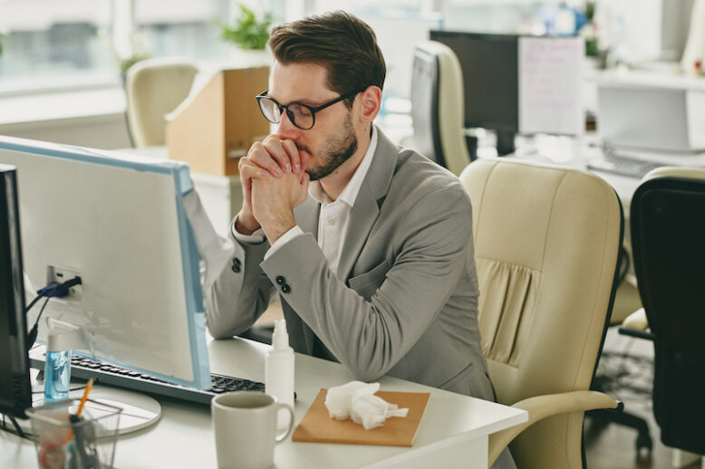 Nervous young businessman in eyeglasses sitting with closed eyes and trying to focus on work in empty office during coronavirus