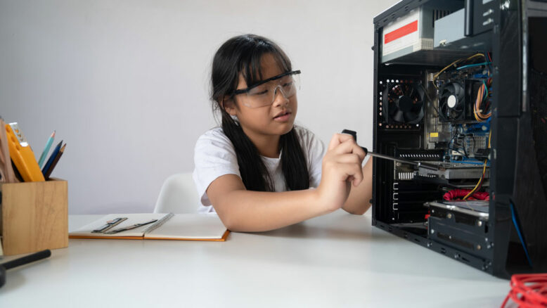 young adorable girl fixing a computer hardware at the modern white working desk.