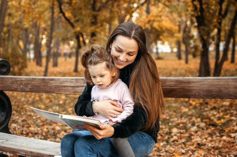 Young female woman babysitter and toddler baby girl read book in autumn park. Happy family mom and toddler outdoors in fall park.