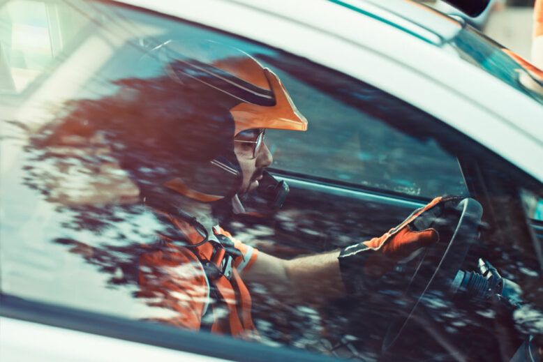 Rally driver, the man in the helmet tensely and seriously looking forward, side view through the car window at the racer participating in the rally
